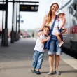 Mother and two kids waiting for train - Stock Photo