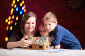 Mutter mit kindern macht lebkuchenhaus — Stockfoto