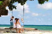 Rodina houpání na tropické pláži — Stock fotografie