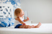 Portrait of playful toddler girl sitting on bed — Stock Photo
