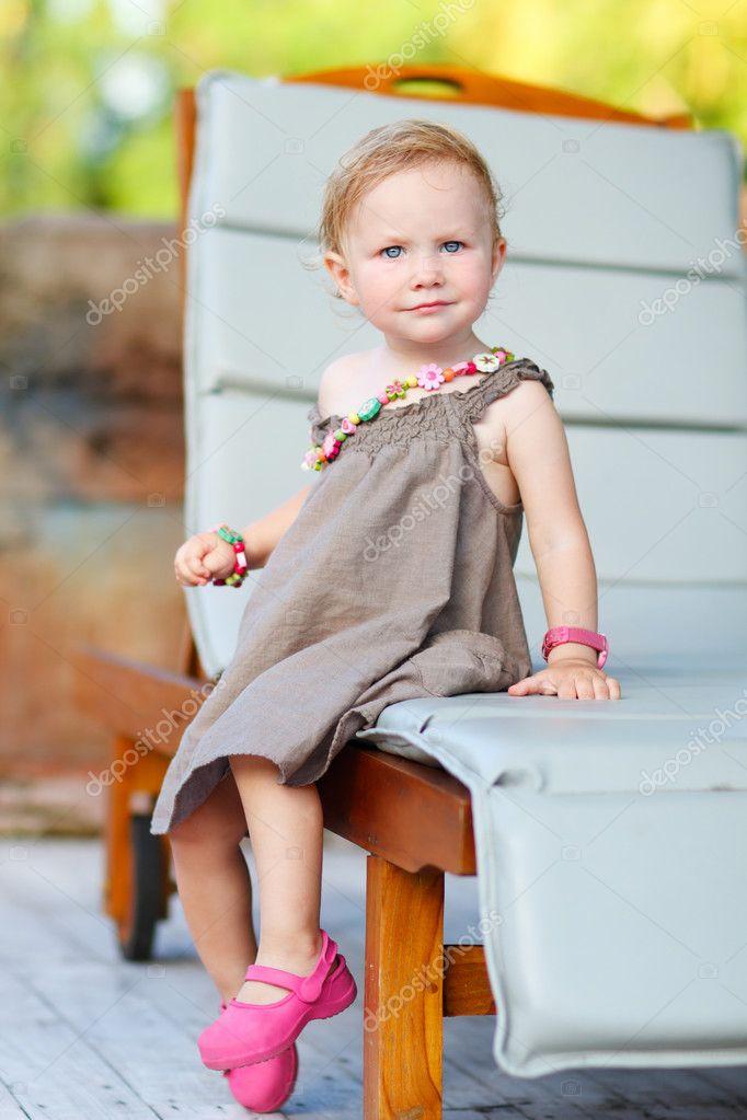可爱的小孩女孩坐在日光浴浴床上的垂直全身画像
