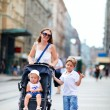 Mother and two kids walking in city center - Stok fotoğraf