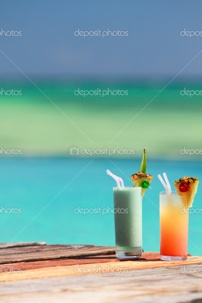 Two tropical cocktails near swimming pool and beach — Stock Photo #3724896