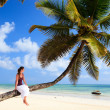 Young woman sitting on palm tree — Foto de stock #3769984