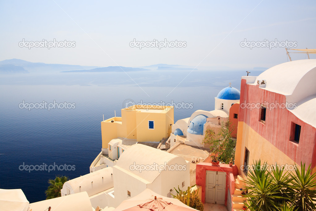 Beautiful church in Oia village overlooks caldera surrounding island of Santorini Greece — Stock Photo #3769823
