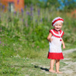 Playful toddler girl in meadow - Stock Photo