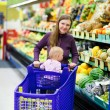 Mother with baby shopping in supermarket — Foto de Stock