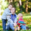 Mother and two kids sitting on grass — Stock Photo #3805475