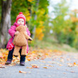 Toddler girl with teddy bear outdoors on autumn day — Stock Photo