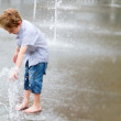 Cute little boy playing with water outdoors — Stock Photo