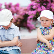 Two unhappy kids outdoors - Stock Photo