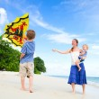 Mother and two kids flying kite — Stock Photo