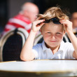 Boy sitting in outdoor restaurant - Stock Photo