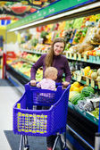 Mother with baby shopping in supermarket — Stock Photo