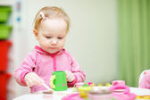 Toddler girl playing with wooden toys — Stock Photo