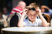 Boy sitting in outdoor restaurant — Stock Photo