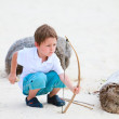 Cute boy playing with bow and arrows — Stock Photo #3856212