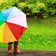Little girl hiding behind umbrella — Stock Photo