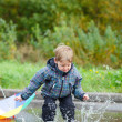 Boy jumping in puddle - Stock Photo