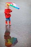Toddler girl with colorful umbrella on rainy day — Stock Photo