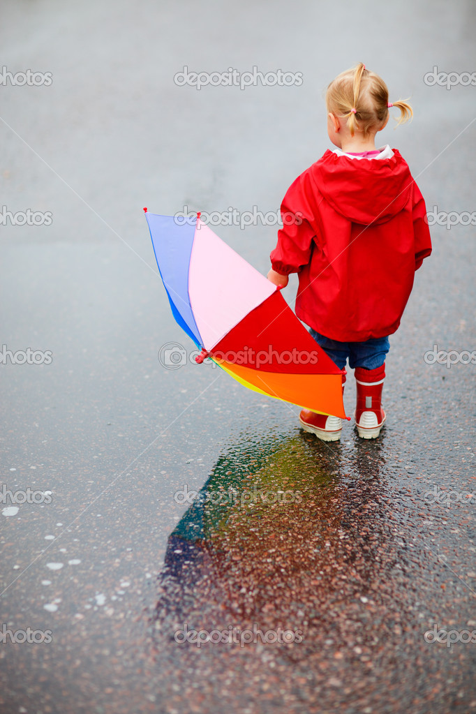 Toddler girl with colorful umbrella outdoors at rainy day — Stock Photo #3856619