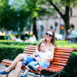 Mother and son on bench in park - Stock Photo