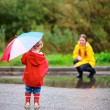 Stock Photo: Mother and daughter outdoors at rainy day