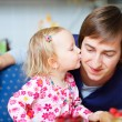Stock Photo: Adorable little girl kissing her father