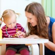 Mother and daughter drawing together - Stock Photo
