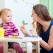 Mother and daughter playing with finger toys — Stock Photo