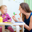 Stock Photo: Mother and daughter playing with finger toys