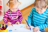 Brother and sister drawing in their room — Stock Photo