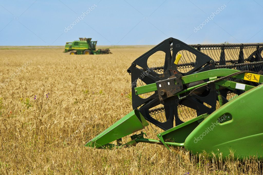 New modern green colored john deere combine harvester during rye earning  Stock Photo #3551101