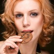 Royalty-Free Stock Photo: Young woman bite a cookie on black