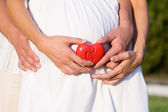 Belly of pregnant with heart in hands — Stok fotoğraf