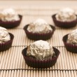 Stock Photo: Choco candies in golden foil on table