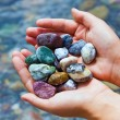 COLORFUL STONES IN HANDS - Stock Photo