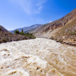 Mountain muddy river under blue sky - Stock Photo