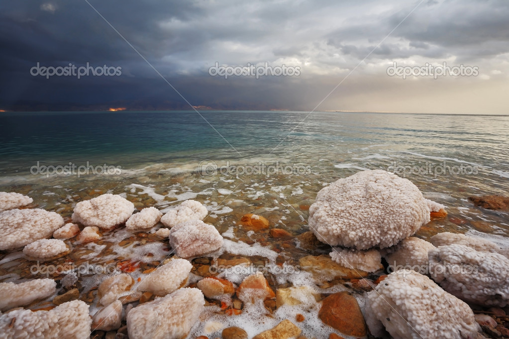 Winter on the Dead Sea. Blue storm cloud, green water and rocks, overgrown with salt — Stock Photo #3857757