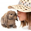 Girl in a straw hat kisses dwarf rabbit. — Stock Photo