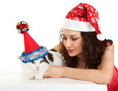 Beautiful girl with a cat in New Year's caps. — Stock Photo