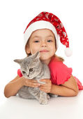 Little girl in New Year's cap with a kitten. — Stock Photo