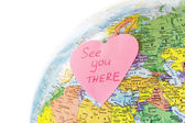 Earth globe and paper heart — Stock Photo