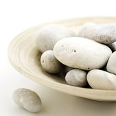 Pebbles in bamboo bowl — Stock Photo