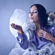 Beautifull woman stylised club fairy blowing off from palm silve - Stock Photo