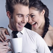 Young attractive couple on grey background — Stock Photo