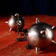 Metal maces on a chain laying on old red carpet. Circus attribut - Stock Photo