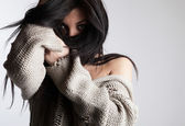 Beautiful young brunette in a woollen sweater pose on a grey bac — Stock Photo