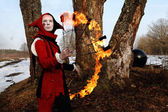 Artistic woman in a suit of fire-clown holds a fiery fan posing — Stok fotoğraf