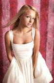 Attractive girl in white dress on a pink background — Стоковое фото